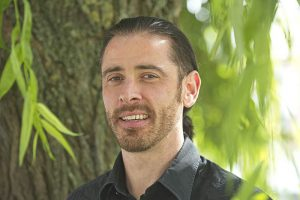 Ben Crawford Mindfulness & Meditation Teacher smiling in front of a tree